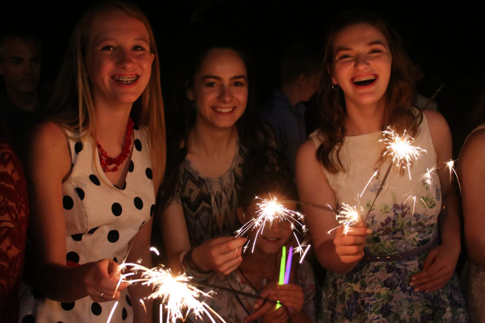 Smiling online Christian homeschooling students are gently illuminated by sparklers at a celebration